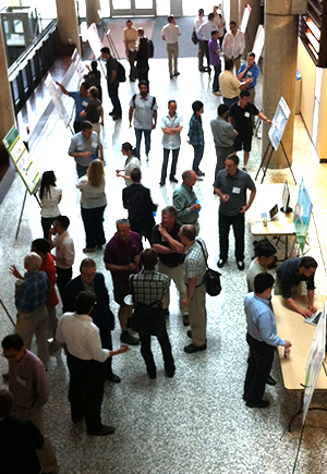 Researchers, students and industry partners participate in a poster and demo session at SAVI's AGM.