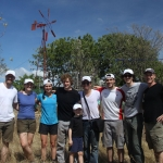 team members with windmill in the background