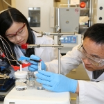 Xueli Zheng, left, and Dr. Bo Zhang set up their device to efficiently split water to store energy as hydrogen. The key is a catalyst made of tungsten, iron and cobalt that is over three times more efficient than the current state-of-the-art. (Photo: Marit Mitchell)