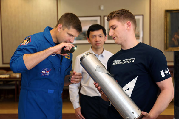 """Astronaut Jeremy Hansen inspects parts of the """"Deliverance"""" hybrid sounding rocket, which will be entered into the Intercollegiate Rocket Engineering Competition in Green River, Utah in June 2016. (Photo: Tyler Irving)"""