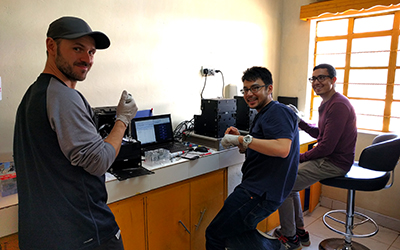 From left: Christian Fobel, Alphonsus Ng, and Julian Lamanna running blood tests on the MR box instruments in their temporary lab in one of the Kakuma health clinics. (Credit: Ryan Fobel)