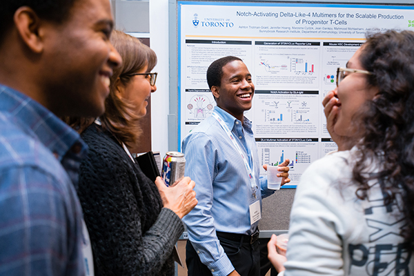 Ashton Trotman-Grant, centre, discusses his poster with Medicine by Design symposium attendees. Trotman-Grant won the Blueline Therapeutic Translation Award for presenting the poster with the greatest commercialization potential. (Credit: Neil Ta).