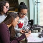 First-year students (from left) Michela Trozzo (Year 1 ECE), Christian Pavlidis (Year 1 CivE) and Elisha Lu (Year 1 ECE) work with a robotic arm in the Systems Control lab. More than 40 per cent of U of T Engineering's first-year students are female, the highest proportion in Ontario. (Credit: Roberta Baker).
