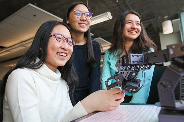 "From left: Xiaoxiao (Maddy) Zhang, Lorna Lan and Brytni Richards (all Year 1 EngSci) work with a robotic arm. I'm so happy to have found the place I belong,"" says Zhang. (Credit: Roberta Baker)."