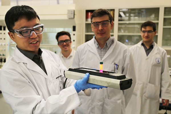 Postdoctoral fellow Fengjia Fan (ECE) shows off a vial of colloidal quantum dots that glow red when excited by UV light. Fan and colleagues Randy Sabatini, Alex Voznyy and Kris Bicanic are using the quantum dots to develop inexpensive, brighter lasers that can be tuned to any frequency in the visible range. (Credit: Kevin Soobrian).