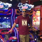 Alumnus Rick Baltman in front of arcade games