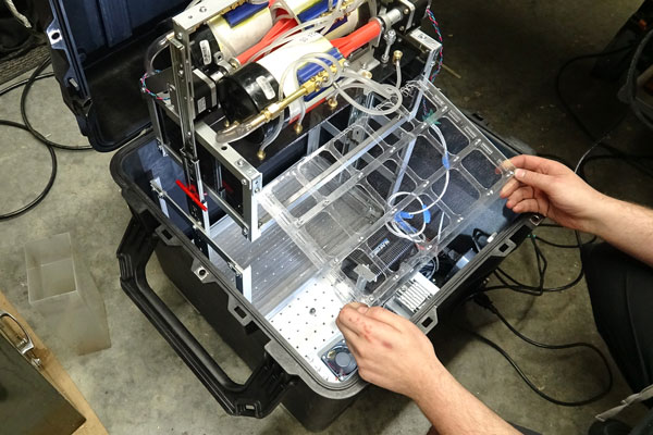 The experimental apparatus is packed inside a box measuring 50 cm x 50 cm x 50 cm and contains pumps and tubes that simulate the operation of a 3D printer. To simulate a molten thermoplastic, the team is using ordinary corn syrup. (Photo: Michael Lawee)