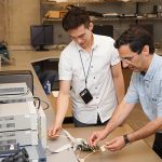 Professor Ali Sheikholeslami demonstrates the features of a test chip designed by his former PhD student Joshua Liang to his MASc student, Danny Yoo, in the lab. (Credit: Jessica MacInnis)