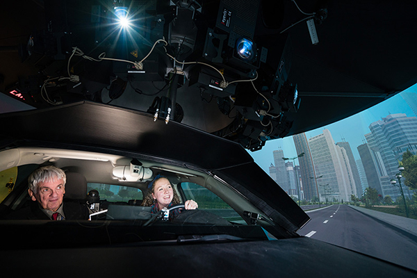 Professor Geoff Fernie (IBBME) and student Philippa Gosine in the DriverLab simulator. DriverLab is the only simulator of its kind in Canada and offers a safe way to study a range of human variables in realistic traffic and weather conditions. (Credit: Neil Ta)