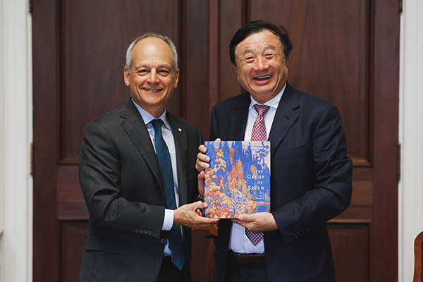 U of T President Meric Gertler presents Huawei CEO Ren Zhengfei with a gift during his visit to the University. (Photo: Tristan Cannon-Sherlock)