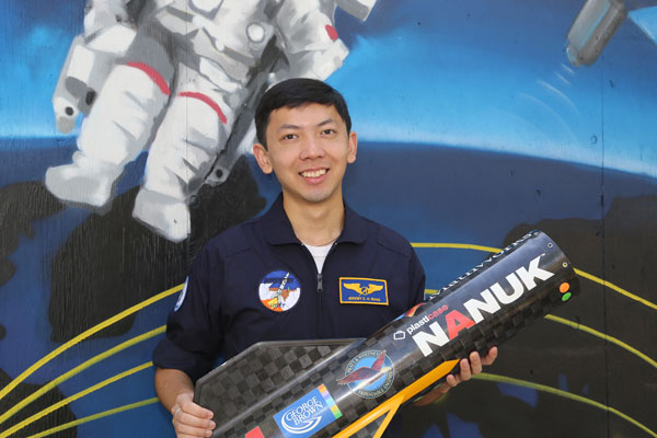 Jeremy Wang holding part of Deliverance, the rocket designed by the University of Toronto Aerospace Team's Rocketry Division. (Photo: Tyler Irving)