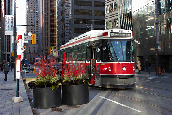 A streetcar stops on King Street in Toronto. A section of the busy east-west street travelling through downtown Toronto has restricted car traffic, and U of T Engineering researchers are collaborating with the City of Toronto and the Toronto Transit Commission to study the pilot project's effects. (Credit: Billy Cabic via Flickr under creative commons license)