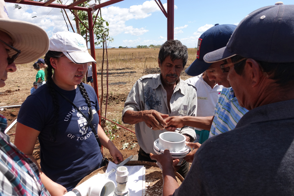 Anna Jiang (MIE MASc candidate) demonstrates her passive water controller for community members in Pedro Arauz, Nicaragua. The device is designed to help farmers make more efficient use of irrigation water. (Image courtesy Anna Jiang)