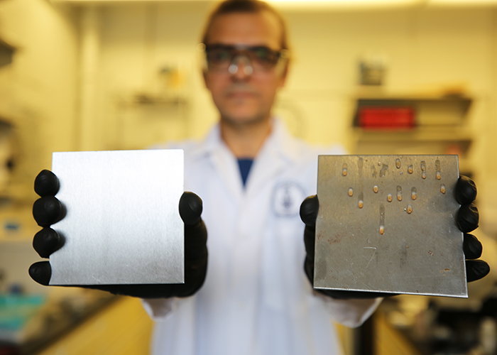 Dr. Tarek Awad, a researcher in U of T's Department of Materials Science & Engineering, shows two samples: at left, a stainless steel surface treated to trap simple cooking oil, and at right, an uncoated surface. The uncoated surface can accumulate food residue and encourage the growth of food-borne pathogens. (Credit: Liz Do)