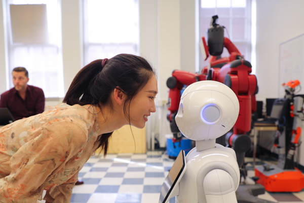 Xinyi Zhang (MIE MASc candidate) interacts with Pepper the robot. (Credit: Liz Do)