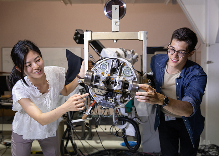 """The Honourable Kirsty Duncan, Minister of Science and Sport, takes a closer look at Professor Angela Schoellig's """"robotic swarming"""" drones, which are designed to be self-contained units that can communicate and observe its closest-neighbour robots and make decisions based on its own observations. (Credit: Tristan McGuirk)"""
