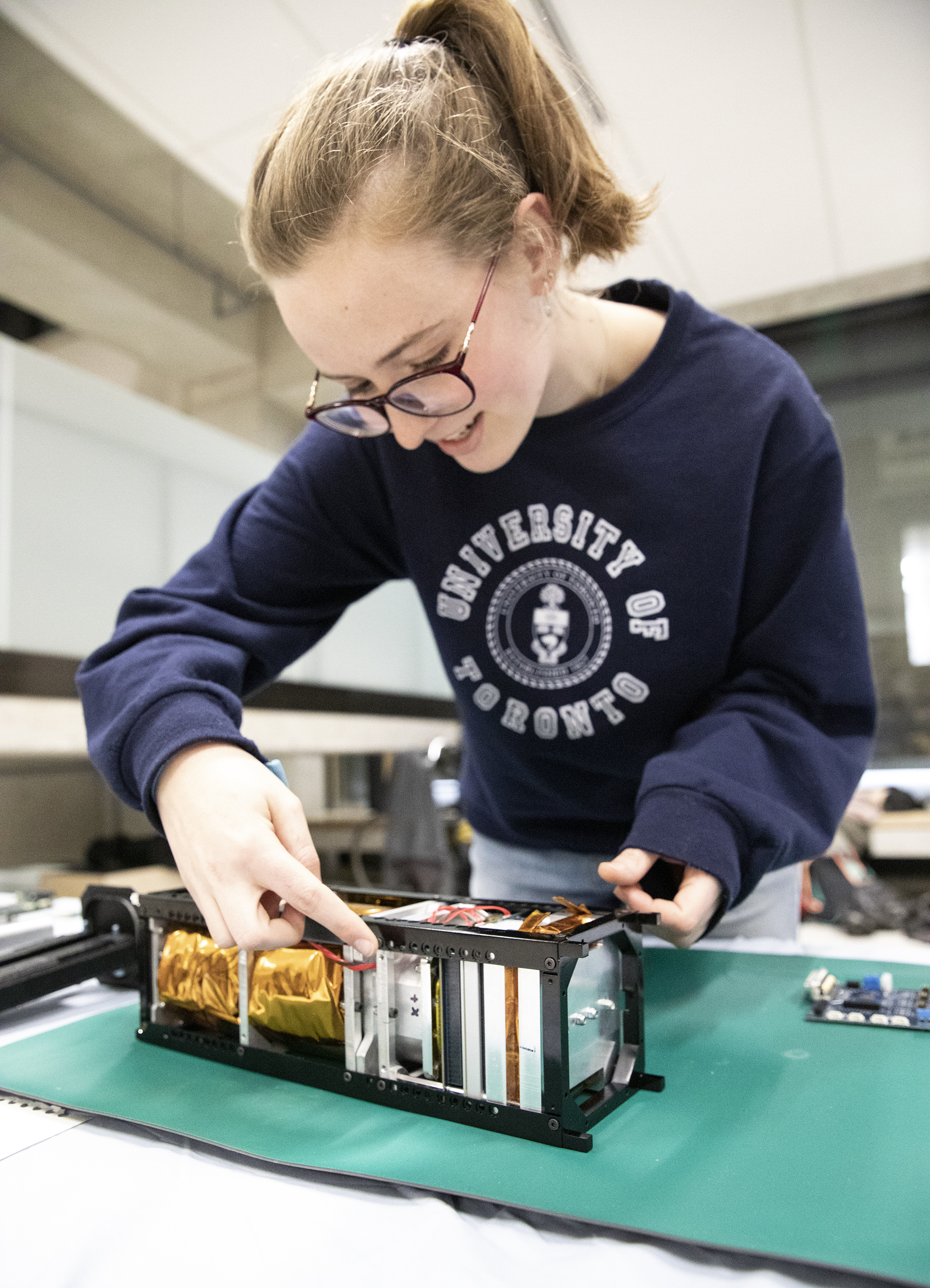 Cassandra Chanen (Year 2 EngSci) shows off the Heron MK II, a cubesat that will take a microbiology payload to space. (Credit: Erica Rae Chong)