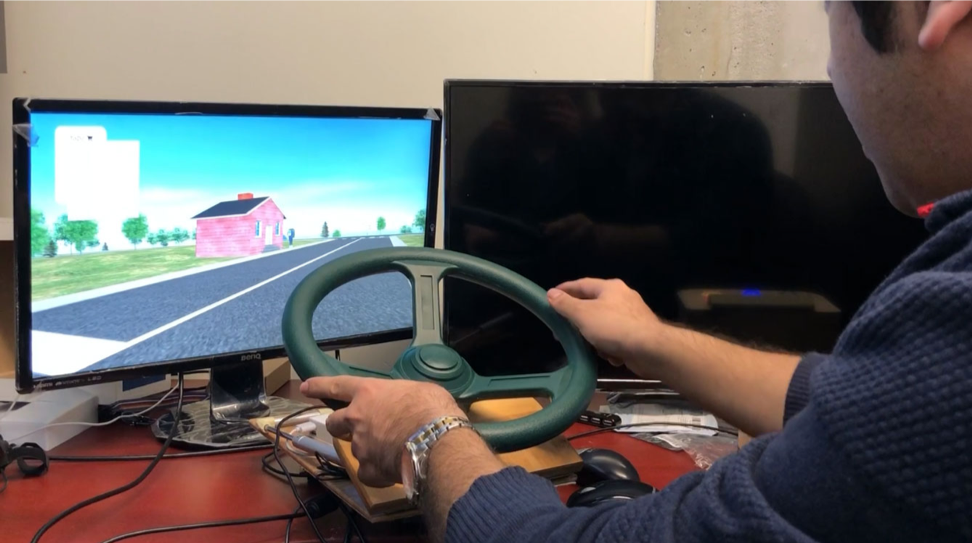 Postdoctoral fellow Farzad Nejatimoharrami demonstrates the driving simulator in Professor Chignell's lab (Photo: Pam Walls).