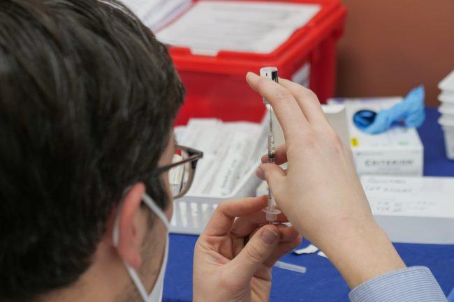 A pharmacist preps a COVID-19 vaccine. (Photo: Steven Cornfield / Unsplash)