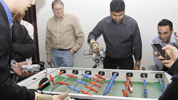Students use their created LEGO forearm prosthetics to compete in a game of foosball.