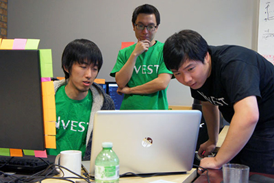 (L-R) Developer James Qiu (Mech 1T5), Chief Technical Officer Jackie Yan (ECE 1T4), and CEO Fredrick Zhou work on Nvest, a social network that helps track the success of investment advice (Photo: Stephanie Lennox).