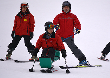 James Xu, at centre, trains using a Sit Ski for his volunteer role as a ski instructor for people with disabilities. (Courtesy: James Xu).
