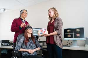 Professor Tom Chau (IBBME, left)) is developing techniques that could allow children with limited mobility, motor control or loss of speech to interact with the world around them. (Photo: Neil Ta)