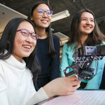 """From left: Xiaoxiao (Maddy) Zhang, Lorna Lan and Brytni Richards (all Year 1 EngSci) work with a robotic arm. I'm so happy to have found the place I belong,"""" says Zhang. (Credit: Roberta Baker)."""