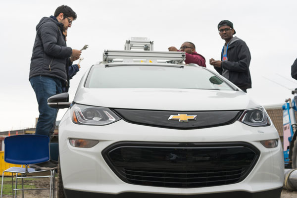 Members of U of T Engineering's AutoDrive team adjust the mounts for autonomous sensors on a donated Chevrolet Bolt. The team has until April to turn the electric vehicle into a self-driving vehicle. (Photo: Alex Lee)