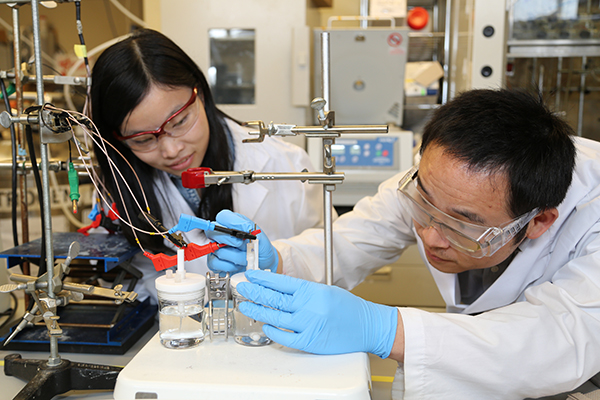 Researchers Xueli Zheng, left, and Bo Zhang test a previous catalyst for the artificial photosynthesis system. The new catalyst works at lower pH, leading to an improvement in the overall efficiency of the system. (Photo: Marit Mitchell)